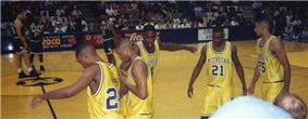 five Black males in gold athletic uniforms in the foreground on the sidelines of an athletic court while a few opposing athletes in green wait in the middle of the court.