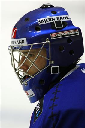 A side shot of an ice hockey players head and shoulder. He is wearing a blue helmet and uniform.