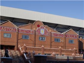 Brick facade of a stadium with a mosaic with a claret background and Aston Villa in gold writing.