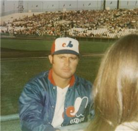 A man in a blue warm-up jacket and red, white, and blue baseball cap looks at the camera. A person with brown hair stands in the right-hand foreground.
