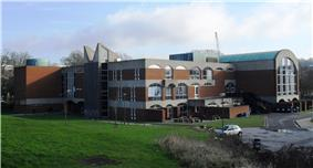 A long, low brick and concrete building with a large curved-roofed wing to the right