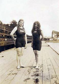 Two female swimmers stand on a wooden pool deck wearing bathing suits that have short sleeves and while full bodied, look like shorts go down to just above the knee