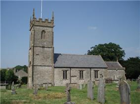Gray stone building with square tower at left hand end. Grass and gravestones in the foreground.