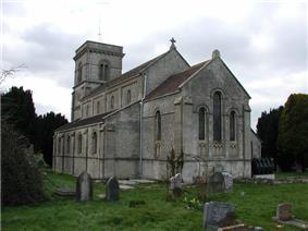 Gray stone building with square tower at far end. Grass and gravestones in the foreground.