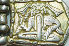 A buckle depicting a sitting man