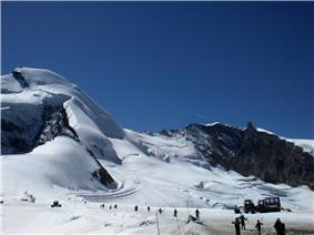A view of mountain slopes, heavily laden with snow.