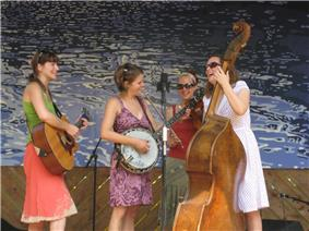 Women playing the banjo, guitar, bass and violin