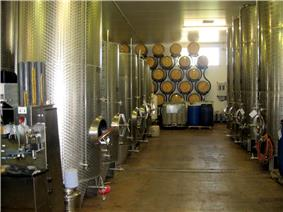 Colour photo showing stainless steel fermentation tanks in the UK.  The tanks are located on both sides of an aisle at the bottom of which oak barrels for aging, stacked on a bracket against the wall can be seen.  The floor is painted and pitched to a drainage channel in the middle of the winery.