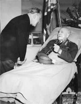 A man lies in a hospital bed, incongruously wearing an Army uniform instead of pajamas. His peaked cap is on the blanket and he holds a baton in his hand. A man in a dark suit and pinstripe trousers bends over to talk to him. In the background are flowers, and a flag.
