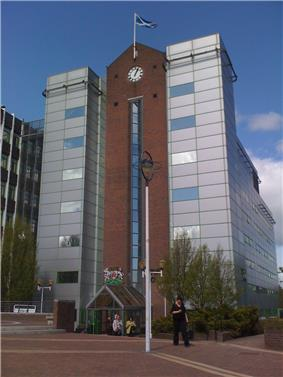 Six-storey office building with facing brick, glass and silver cladding with clock feature.