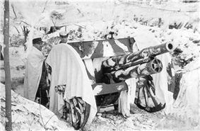 A cannon wears a white blanket on the snow and two men pose side of it.