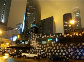 After dark, hundreds of silver stars on the walls. In front of tall buildings downtown, cars parked in front.