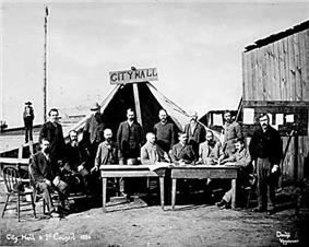 Men standing and sitting around two tables, facing the camera. A large tent behind them has a wooden sign that reads