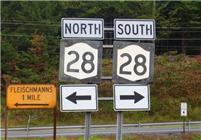 Two road signs with the number 28 in black on a white background with