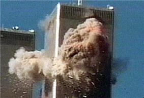 A high-rise tower covered by debris on two of its faces. In the lower left corner is a similar building.