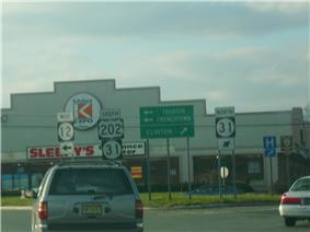The view from a car windshield of signs for circle 12 circle 31 and U.S. 202 in the middle of a setting sun