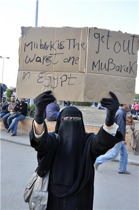 Woman covered in black except for her eyes, holding a sign