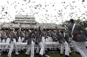 Outdoors men in gray uniforms throwing hats in the air.