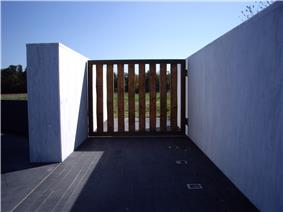 A large wooden gate in a marble wall