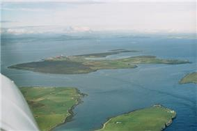 An aerial view of Flotta from the south-west. The oil terminal is visible to the centre-left, with the airstrip further to the left. South Walls is at the bottom and bottom left, and Switha at the extreme right.