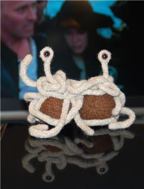 small handmade knit Flying Spaghetti Monster sitting on a table with people dressed as pirates in background.