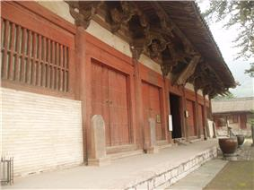 The front of a Chinese temple building. It is painted white with red trim.