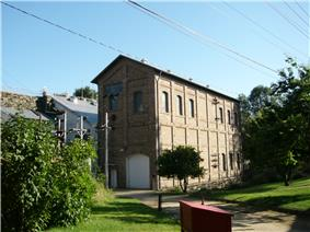 Photograph of the Folsom Powerhouse, a tall, narrow masonry building with power lines overhead and the dam in the background.