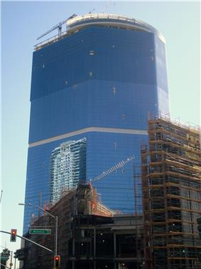 Ground-level view of an under construction 60-story building; The building's lower floors are covered in glass, but its upper 30 floors are unfinished and uncovered.