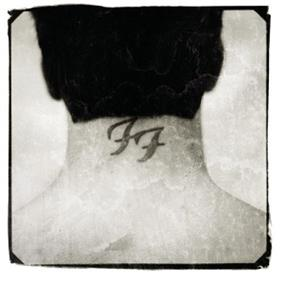 Black and white photograph of the back of Dave Grohl's head. A tattoo of the Foo Fighters logo is seen on his neck.