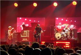 A crowd of people standing before a stage lit by four lights from above. On the stage, from left to right, is a man with a guitar, a man dressed in black holding a guitar, and a man sitting behind a drum set.