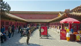 An area enclosed on three sides by red walls in traditional Chinese architectural style. All have screened windows and entrances; behind the rear wall is an even higher one. In the middle are tables, and at the right foreground is an ice cream cart and a red umbrella