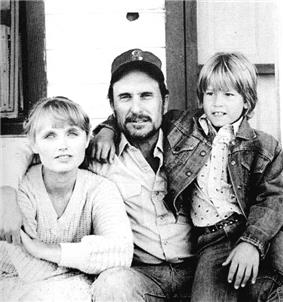 A black-and-white image of a bearded man wearing a baseball cap, sitting on the front porch of a wooden house, with his right arm around a smiling woman wearing a sweater, and his left arm around a smiling young boy sitting on his lap.