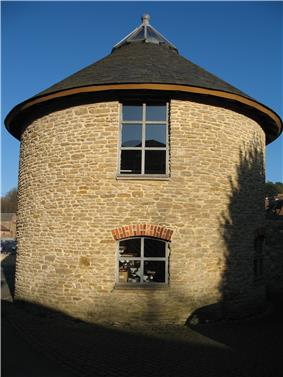 Circular stone building with slate roof.