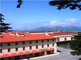 Photograph of docks and red-roofed, stucco warehouses at the San Francisco Port of Embarkation, U.S. Army. The Golden Gate Bridge spans the background of the picture.