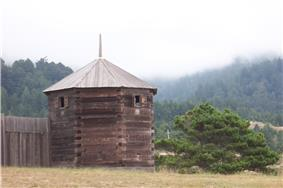 Photograph of a reconstructed blockhouse and palisade wall at Fort Ross, a Northern California forestscape in the background.