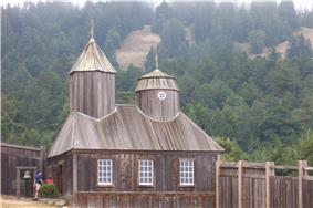 Photograph of the reconstruction of the Fort Ross Chapel, a wooden walled and roofed building with an evergreen-covered hillside behind.
