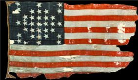 Photograph of a faded and torn United States flag