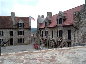 A photograph of two stone buildings with red roofs, surrounding a stone-paved central area. The buildings have entrances on two levels, with wooden stairs outside leading to the doorways on the upper level. An American flag is visible waving in the gap between the buildings.