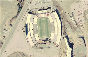 An aerial view of a large sports stadium with a four-lane road next to it on the left and the beginnings of a similar structure at lower right