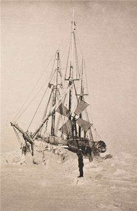 Semi-frontal view of a frost-covered ship surrounded by hummocks of ice. A lone figure stands on the ice nearby.