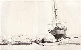 Front view of ship showing it listing to the right. It is surrounded by ice, but in front of the ship a narrow channel of open water is visible. The scene is watched by a man standing on the ice.