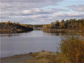 A small body of water at the base of a beach in the foreground, with a passage between two high, stony areas and more land behind it. All the land is covered in forest with a mix of deciduous and evergreen trees.