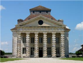 A large neo-classical white stone building, the triangular pediment is supported by six rough pillars.