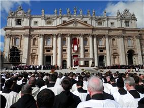 The exterior of the basilica on a sunny day. In the foreground, hundreds of robed priests look towards a podium where there is an altar, and a group of white robed figures attends the Pope.