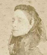 Faded sepia photograph showing the head and shoulders of a lady wearing a veil over her hair