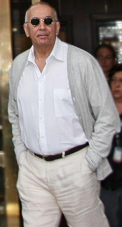 A man wearing a white shirt with a grey jacket and circular sunglasses