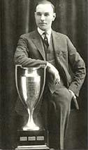 man in suit leaning on trophy in front of him