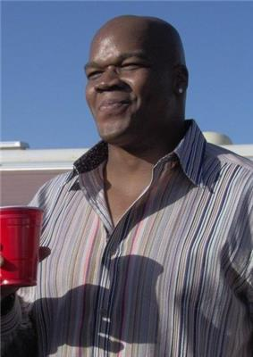 A bald black man in a vertically striped shirt, facing left, smiling and holding a red cup