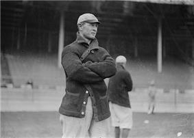 A man wearing a dark-colored coat and baseball cap with his arms crossed stands on a baseball field; two similarly dressed men are behind him.