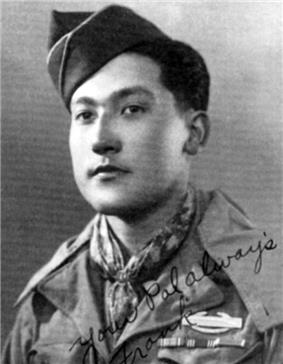 Head and shoulders of a young man with a garrison cap tilted over his right ear wearing a scarf tied around his neck and a military jacket with three ribbon bars and a pin on the left breast. Written over the lower right of the photo are the words
